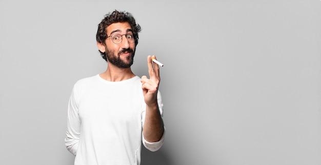 Giovane uomo barbuto pazzo con una sigaretta. concetto di non fumare.