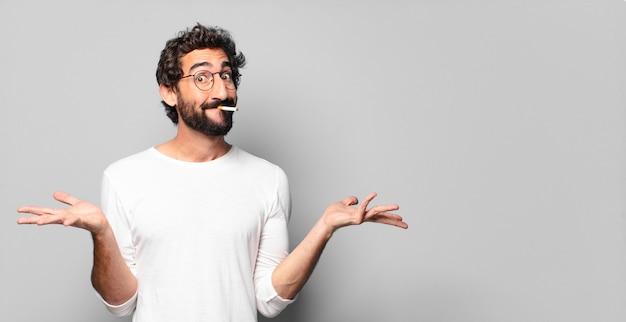 Giovane uomo barbuto pazzo con una sigaretta. nessun concetto di fumo.