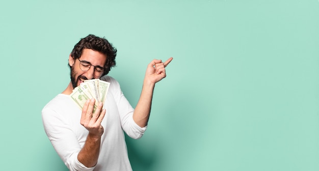 Giovane uomo barbuto pazzo con banconote in dollari