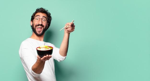 Giovane uomo barbuto pazzo con una ciotola di ramen di noodle