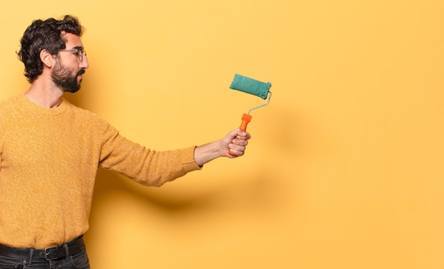 Giovane uomo barbuto pazzo con un rullo di vernice che dipinge e cambia il colore della parete