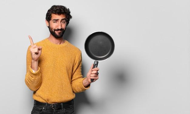 Giovane uomo barbuto pazzo con una padella. concetto di cuoco