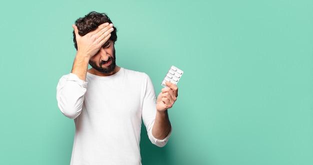 Giovane uomo barbuto pazzo con una compressa di pillole