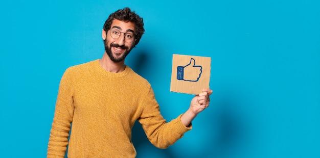 Giovane uomo barbuto pazzo con un social media come un foglio