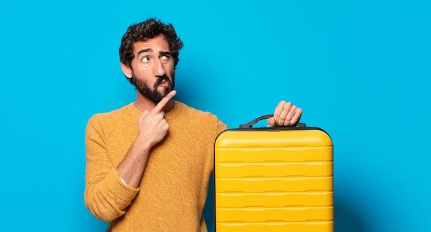 Giovane uomo barbuto pazzo con una valigia