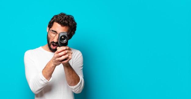 Giovane uomo barbuto pazzo con una fotocamera super 8