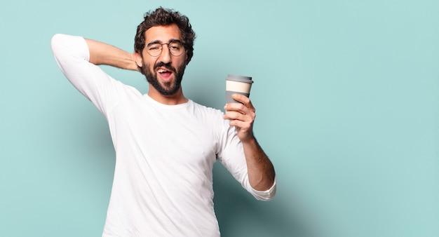 Giovane uomo barbuto pazzo con un caffè da asporto