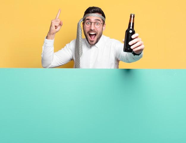 Giovane uomo d'affari pazzo con una bottiglia di birra che celebra la buona notizia