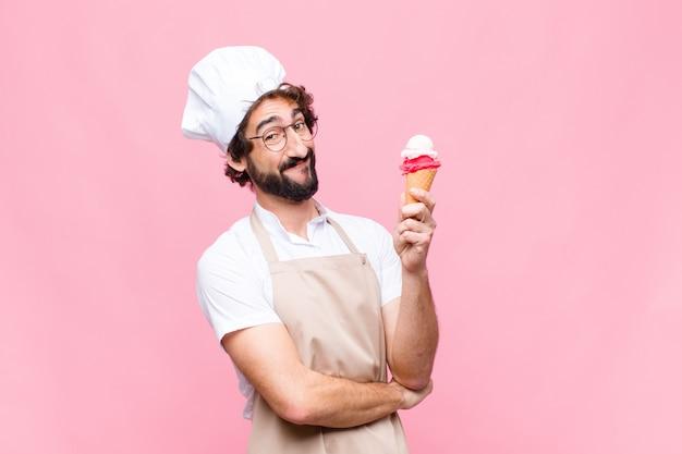 Uomo giovane chef pazzo con un gelato sulla parete rosa