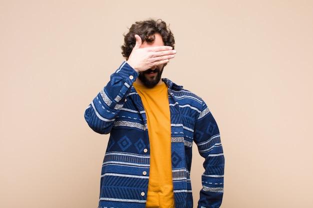 Giovane pazzo uomo freddo che copre gli occhi con una mano sentirsi spaventato in attesa di una sorpresa contro la parete piatta