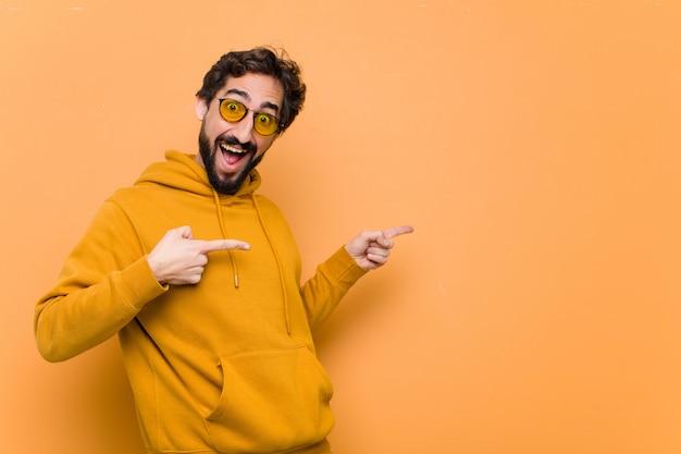 Giovane uomo freddo pazzo che punta al lato sulla parete arancione