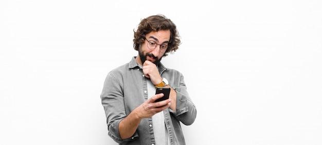 Giovane uomo cool pazzo utilizzando il suo smartphone sul muro bianco