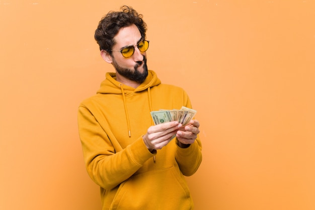 Giovane uomo cool pazzo con banconote in dollari sulla parete arancione