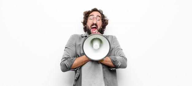 Giovane pazzo uomo freddo con un megafono contro il muro bianco