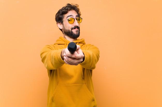 Giovane pazzo fresco con un microfono contro il muro arancione