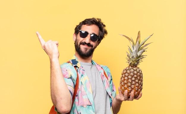 Uomo giovane viaggiatore pazzo che celebra con successo una vittoria e che tiene un ananas