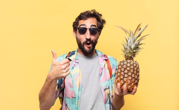 Espressione felice dell'uomo giovane viaggiatore pazzo e che tiene un ananas