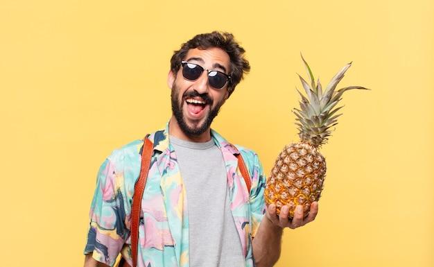 Giovane viaggiatore pazzo uomo ha sorpreso l'espressione e tenendo un ananas