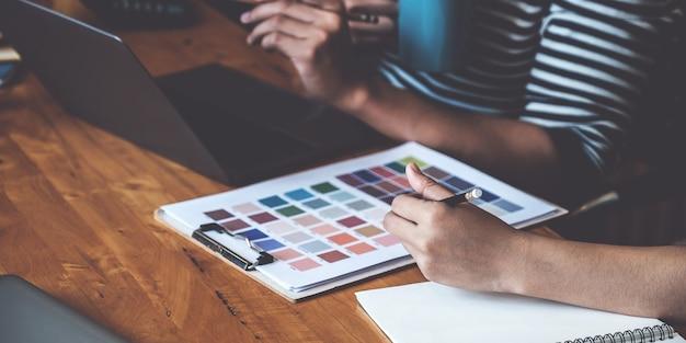 Giovane designer creativo che tiene matita e mano che punta alla lastra di colore