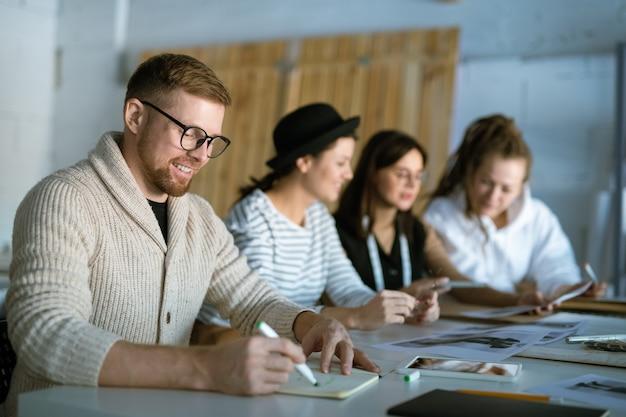 Giovane designer di moda creativo disegno schizzo in quaderno su sfondo di colleghi che lavorano sulla nuova collezione