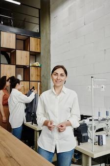 Giovane stilista creativo in jeans e camicia bianca in piedi davanti alla telecamera in officina