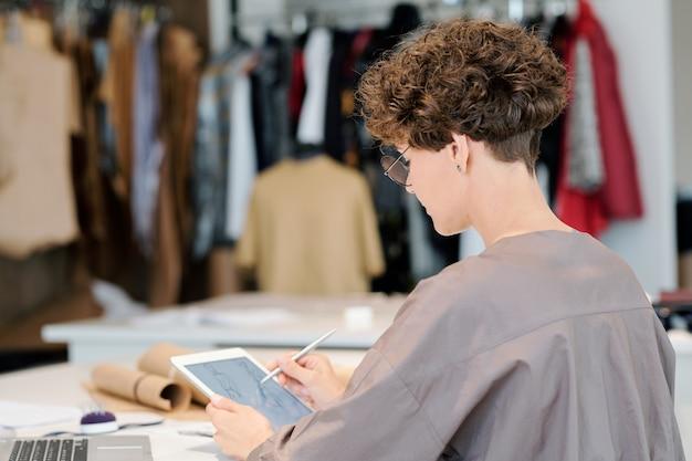 Giovane stilista creativo con tablet che fa schizzi digitali di nuovi modelli per la raccolta