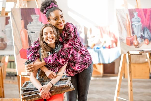 Giovani studenti creativi multietnici seduti durante la pausa nello studio universitario per dipingere