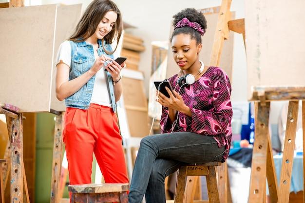 Giovani studenti creativi multietnici seduti con i telefoni durante la pausa nello studio universitario per dipingere