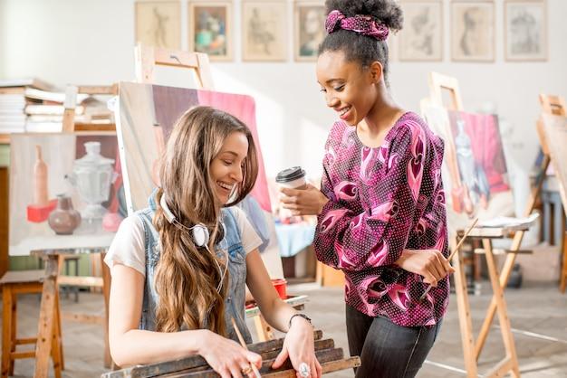 Giovani studenti creativi multietnici che parlano durante la pausa nello studio universitario per dipingere