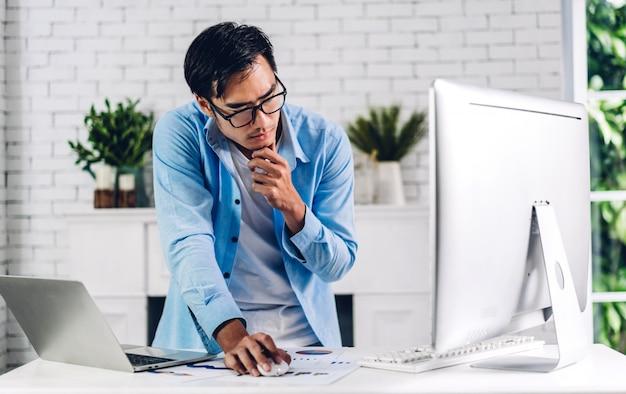 Giovane uomo asiatico felice sorridente creativo che si rilassa facendo uso del funzionamento del desktop computer e della videoconferenza che incontrano chat online a casa. lavorare da casa concetto