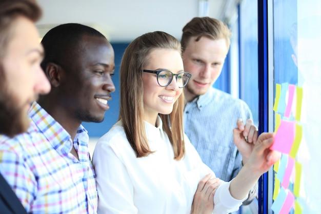 Giovani imprenditori creativi di avvio che si incontrano in un ufficio moderno che fanno piani e progetti con adesivi post su vetro