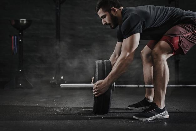 Giovane atleta in forma trasversale che prepara il bilanciere per il sollevamento pesi in palestra