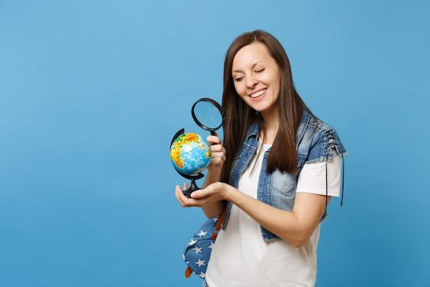 La giovane studentessa graziosa curiosa in vestiti del denim con lo zaino che guarda il globo del mondo con la lente d'ingrandimento impara la geografia isolata su fondo blu. istruzione al college universitario di scuola superiore.