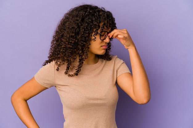Giovane donna afroamericana riccia che esprime emozioni isolate