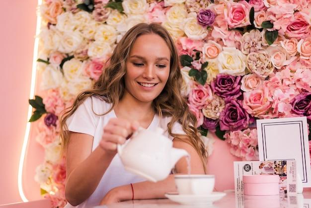 La giovane donna bionda riccia beve il tè nella caffetteria