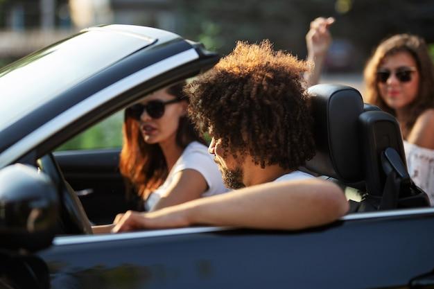 Il giovane uomo dai capelli scuri ricci e due belle ragazze dai capelli scuri in occhiali da sole sono seduti in una cabriolet nera. .