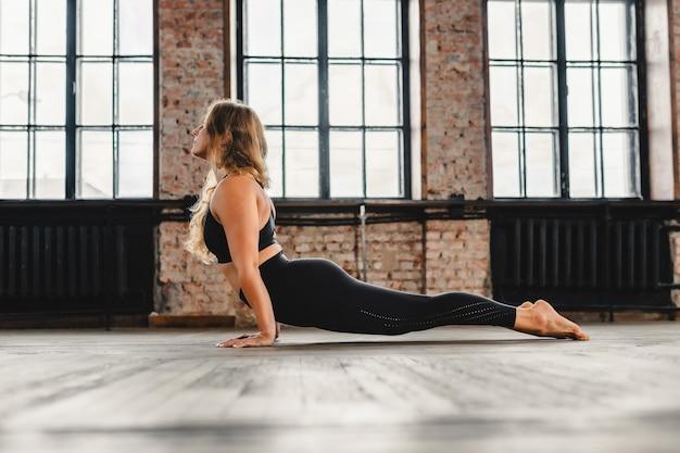 La giovane femmina riccia fa complesso di esercizi di yoga di allungamento sul pavimento del corridoio del soppalco e sorride. positivo, meditazione, concentrazione. urdhva mukha svanasana - posizione del cane a testa in su.