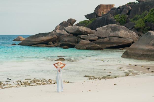 Giovane ragazza riccia sull'isola tropicale in abito di chiffon blu.