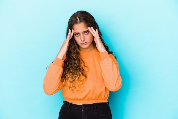 Giovane donna capelli ricci isolata avendo un mal di testa, toccando la parte anteriore del viso
