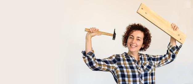 La giovane ragazza caucasica dai capelli ricci tiene una tavola di legno e un martello.
