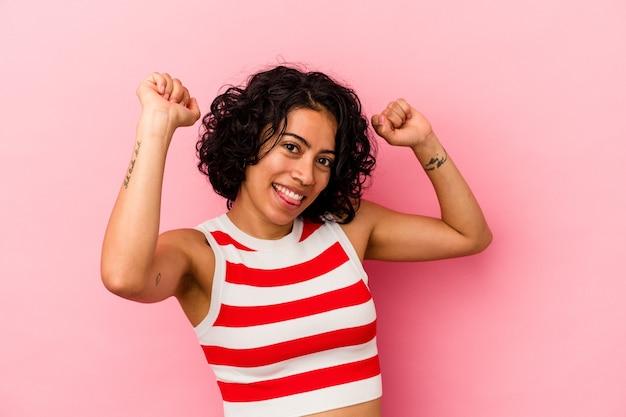 Giovane donna latina riccia isolata su sfondo rosa che celebra un giorno speciale, salta e alza le braccia con energia.