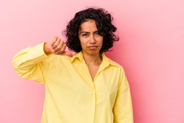 Giovane donna latina riccia isolata su sfondo rosa che mostra un gesto di antipatia, pollice in giù. concetto di disaccordo.