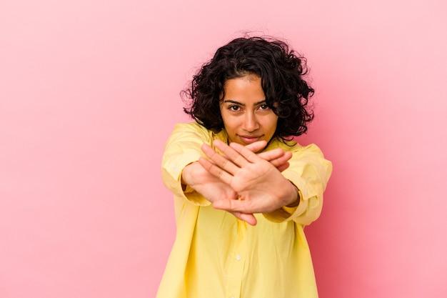 Giovane donna latina riccia isolata su sfondo rosa in piedi con la mano tesa che mostra il segnale di stop, impedendoti.