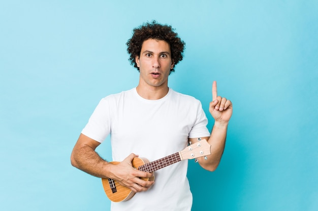 Giovane uomo riccio che suona l'ukelele con una grande idea, il concetto di creatività