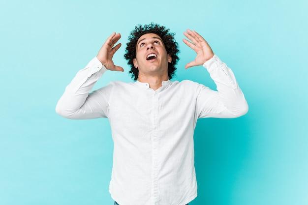 Giovane uomo maturo riccio che indossa una camicia elegante che grida al cielo, alzando lo sguardo, frustrato.