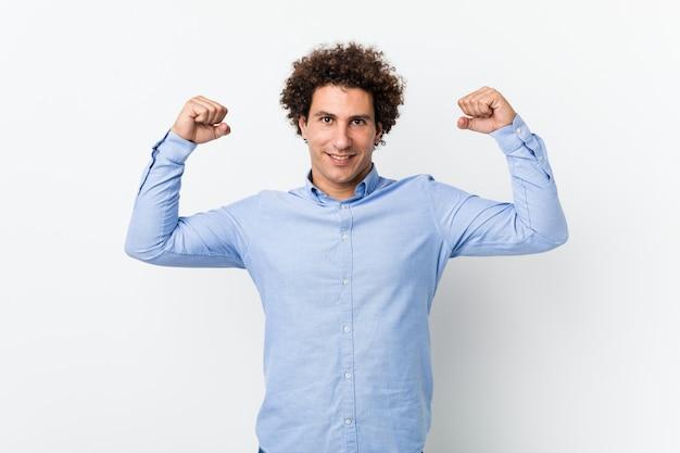 Giovane uomo maturo riccio che indossa una camicia elegante che mostra gesto di forza con le braccia, simbolo del potere femminile