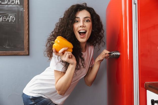 Giovane donna riccia 20s che tiene carta dolce e apre il frigorifero mentre cucina la cena nell'interno della cucina a casa