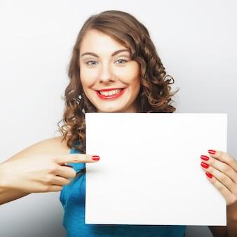 Giovane donna riccia che tiene scheda in bianco