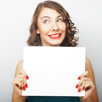 Giovane donna riccia che tiene carta in bianco