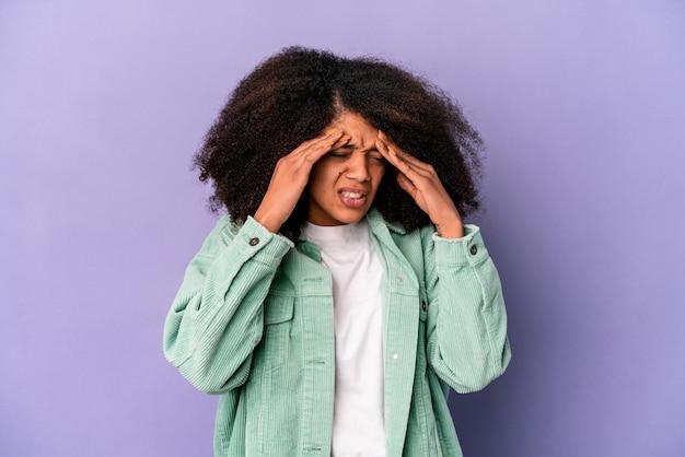 Parete isolata giovane donna riccia con mal di testa, toccando la parte anteriore del viso